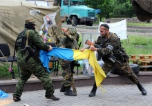 TOPSHOTS TOPSHOTS Pro-Russian fighters of Vostok (East) battalion rip apart an Ukrainian flag outside a regional state building in the eastern Ukrainian city of Donetsk on May 29, 2014. Armed militiamen of the Pro-Russian Vostok batallion surrounded the regional state building in Donetsk before entering, demanding that the activists of the so-called People's Republic of Donetsk leave the premises and detaining several of them. Pro-Russian rebels downed a Ukrainian helicopter on May 29, killing 12 soldiers including a general and undermining president-elect Petro Poroshenko's fervent vow to crush the bloody seven-week insurgency roiling the industrial east. AFP PHOTO/ VIKTOR DRACHEVVIKTOR DRACHEV/AFP/Getty Images